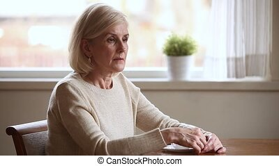 Lonely mature woman sitting at table lost in sad thoughts -...