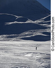 lonely off piste skier - a lone skier skis in fresh powder...