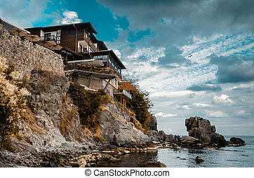 lonely old house on a rock cliff on seashore
