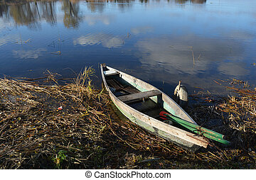 Lonely old wooden boat on lake coast and reflections