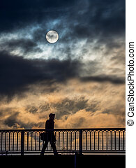 lonely person with clouds and sun - a lone person walks...