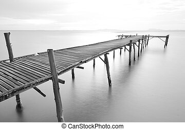 lonely - balck and white picture of old bridge to the sea.