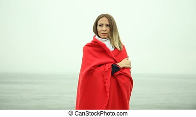 Lonely girl sad pensive woman in red blanket standing on the sea shore. Loneliness and sadness.