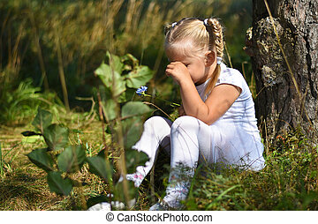 Lonely sad little girl in a white dress and a flower in her hand was lost in the woods, sitting near a tree and crying during day
