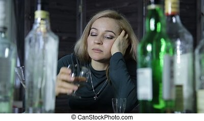 lonely sad woman drinks alcohol, lot of empty bottles around...