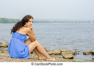 Lonely sad young girl sitting on the river bank