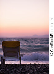 Lonely seashore with sun bed in sunset