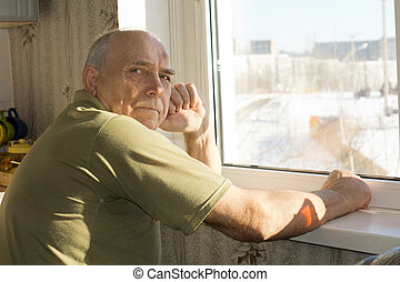 Lonely senior man sitting at a window turning to look at the camera with a serious thoughtful expression