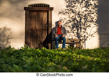 Lonely senior man sitting on bench in front of old house, eyes closed.