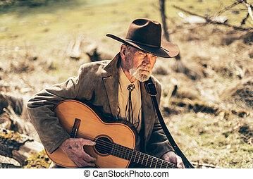 Lonely senior man sitting strumming his guitar