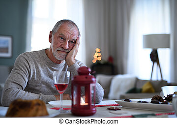 Lonely senior man with wine sitting at the table indoors at Christmas, solitude concept.