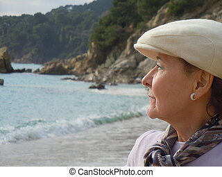 lonely senior woman at the beach - profile of senior woman...