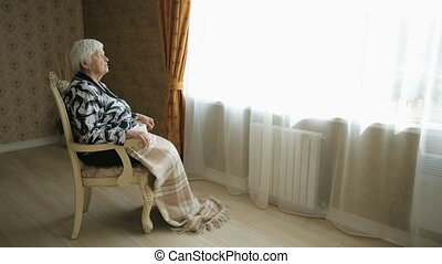 Lonely Senior Woman - Lonely old woman sitting on a chair in...