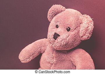 Lonely teddy bear on a dark background looking sad