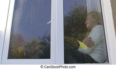 Lonely teenage girl near window crying in rainy autumn day