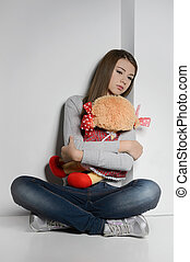 Lonely teenage girl. Sad teenage girl sitting on the floor and hugging a toy