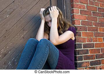 Teenage girl huddled in old doorway.