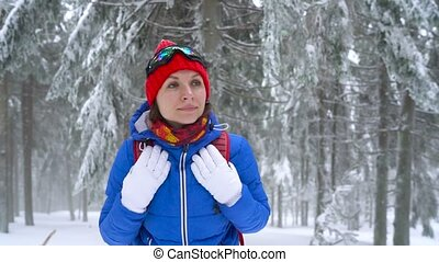 Lonely tourist girl walking on a winter snow-covered coniferous forest in the mountains. Frosty harsh weather