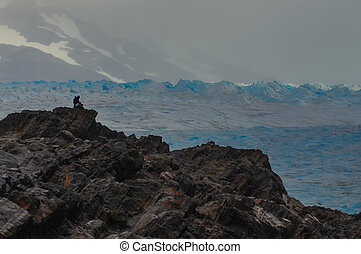 Lonely tourist in front of a glacier field