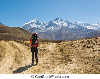 Lonely trekker on a crossroad of two roads towards mountains.