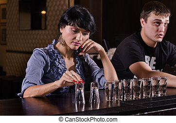 Lonely woman alcoholic sitting at a bar counter with a long...
