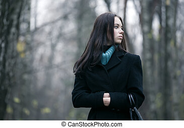 Lonely woman in a forest. Autumn november season.