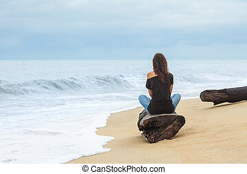 Lonely woman sitting on the tropical beach