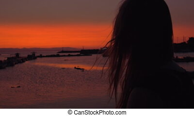 Lonely woman staring at small harbour in the evening - Slow...