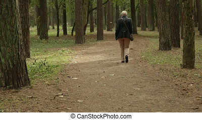 Lonely Woman walks in park. Autumn daytime. Smooth middle dolly shot