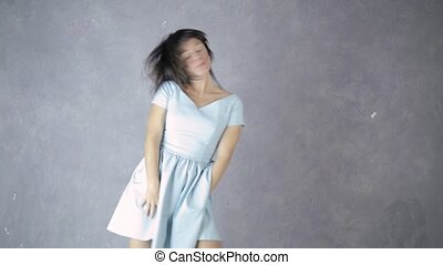 lonely young attractive woman in blue dress laughs and...