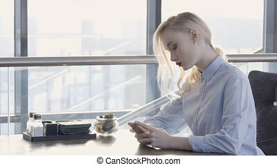 Lonely young blond woman is sitting in a cafe with a phone.