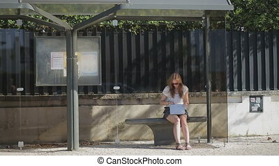 Lonely young girl waiting at bus stop with smart phone in blue skirt and sunglasses, summertime