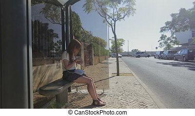 Lonely young girl waiting staying at bus stop in blue skirt and sunglasses, summertime, traffic