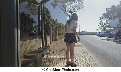 Lonely young girl waiting staying at bus stop with smart phone in blue skirt and sunglasses, summertime, traffic