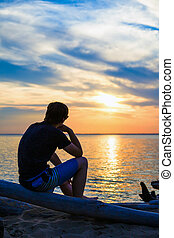 Lonely Young Man at Seaside - Young Man sit in a Log and...
