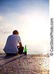 Lonely Young Man outdoor - Young Man with a Beer sit at...