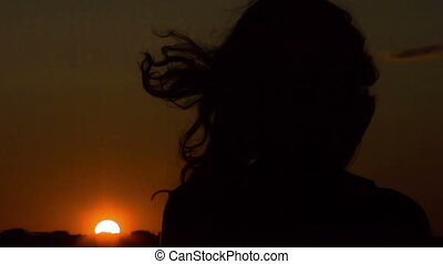 """Lonely young woman looking at sunset, thinking, wind playing with her hair"""