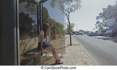 Lonely young woman waiting at glass bus stop in skirt with smart phone and handbag, summertime