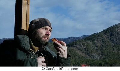 lonesome bearded man standing on observation deck looking on a mountain and drinking coffee or tea from big cup