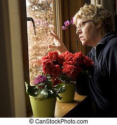lonesome woman - lonesome elderly woman looking outside