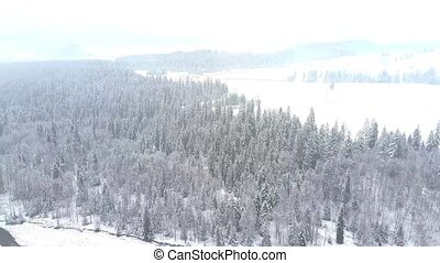 Long aerial clip of a snowy winter scenery in southern...