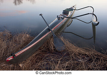 long and slim racing outrigger canoe on a calm lake
