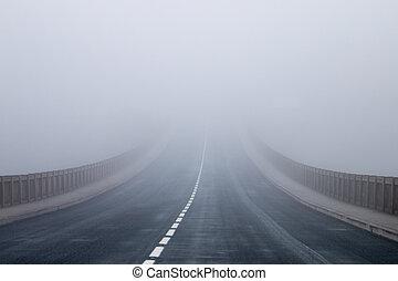 Long asphalt road in the fog