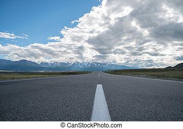 Long asphalt road. Mountains in the horizon.