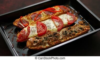 Long baguettes pizza sandwiches with tuna, mushrooms, tomatoes and melted cheese on a metal baking tray placed on the table. Homemade food. Top view.