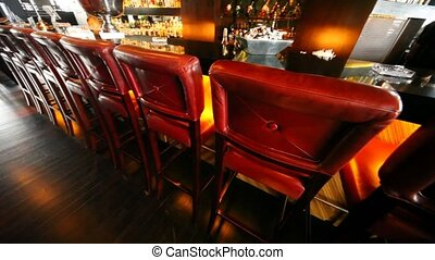 Long bar counter is filled by bottles with spirits nearby there is man