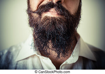 long beard and mustache man with white shirt on gray...