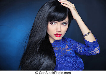 Long Black Hair. Beautiful model girl with healthy straight shiny hair and sensual lips isolated on blue dark background. Beauty Brunette Woman.