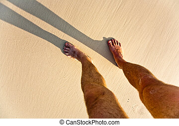 long body shadow of a man in the fine sand of the beach, feet is