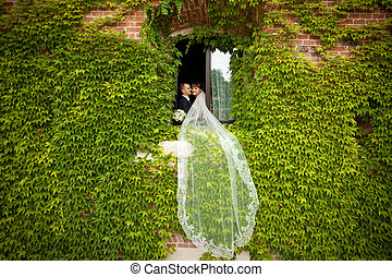 Long bride's veil hangs from the window while she stands with a groom